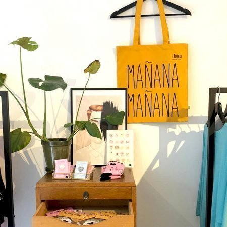 Gele tas aan kledinghanger in winkel met plantjes
